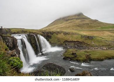Long Exposure of Kirkjufellsfoss with Kirkjufell Mountain in the background, obscured by fog (Iceland)