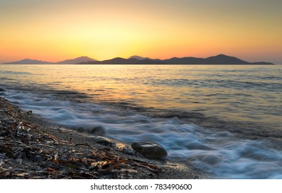 A long exposure landscape of beautiful sunset at the mediterranean sea beach near concrete bridge with orange sky and a mountains on the horizon
