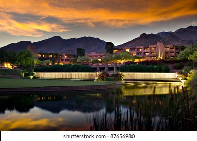 Long exposure of a luxury hotel resort.  A golf course and pond is in the foreground and foothill mountains in the background.