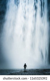 Long exposure of the massive Skogafoss waterfall, South Iceland, with a person in front to show scale