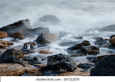 long exposure of misty sea and rocks on the beach in the morning.