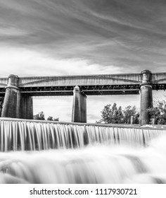 Long Exposure Neutral density black and white shot of a waterfall with a train bridge in the background, NSW, Australia