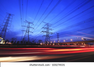 long exposure of night car rainbow light traffic on a highway and transmission tower at night skyline