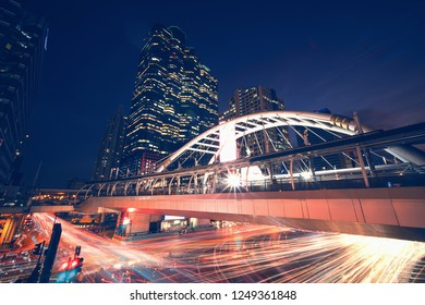 long exposure night cityscape image of central of business area in Bangkok Thailand at sky trainstation junction with traffic light trails ad skyscraper as background