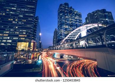 long exposure night cityscape image of central of business area in Bangkok Thailand at sky trainstation junction with traffic light trails and skyscraper as background