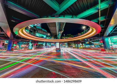 Long exposure night cityscape image of central of business area in Bangkok Thailand at sky trainstation junction with traffic light trails and skyscraper as background stock photo