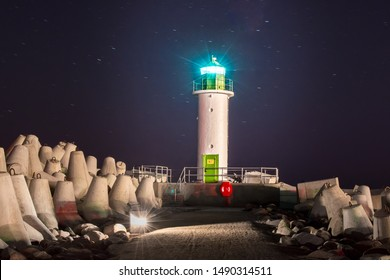 Long exposure night photography with bulwark, breakwater stones and old lighthouse with blue light, Ventspils city, Latvia