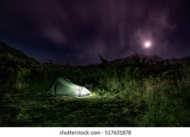 Long exposure night scene of a green tent, lit from the inside, the moon and clouds