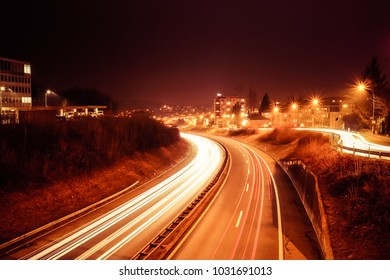"""Long exposure night shot an highway with vehicles light trails, buildings and public lighting in the background, in """"Fribourg"""", Switzerland"""