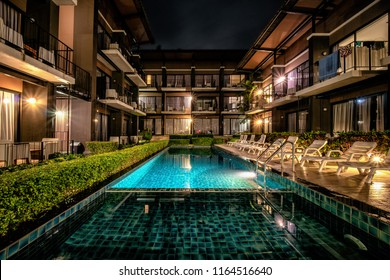 long exposure night shot image of poolside resort building with swimming pool and pool chairs along pool side at Lalune beach resort Samed island Rayong Thailand