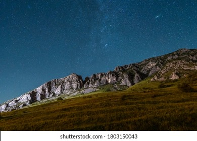 Long exposure night sky astrophotography with the landscape of a mountain above which is the clear and starry blue sky where you can see the Milky Way and the Andromeda Galaxy. Celestial events.