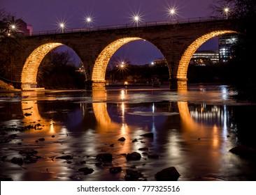 Long exposure night time twilight blue hour shot of Stone Arch Bridge Minneapolis Minnesota on the Mississippi River