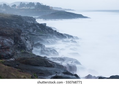 Long exposure of ocean waves running up onto eroded, exposed lava rock creates a spooky fog effect