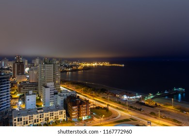 Long exposure panoramic night view of the coastline at a holiday resort in Punta Del Este, Uruguay: the quiet empty beach, the calm water, the car lights passing and the illuminated harbor at the back