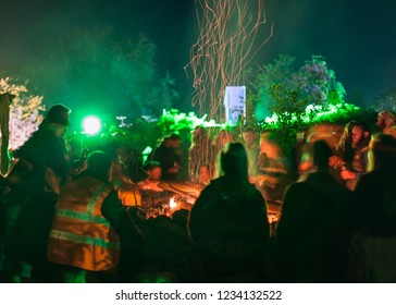 A long exposure of people sitting around a camp fire