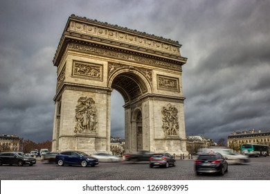 Long exposure photo of the Arc De Triomphe with ominous clouds overhead and traffic circling the roundabout, Paris, France
