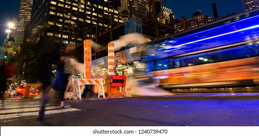 Long exposure photo of buses and people crossing an intersection in New York City while steam coming out from the manhole. Manhattan, New York, United States.