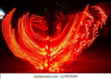 Long exposure photo with dancing girls dressed in led light costumes.