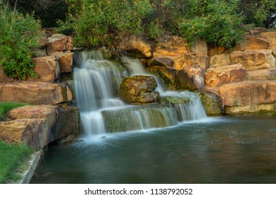 A long exposure photo to induce motion-blur of a man-made waterfall in Frisco's Central Park in Texas.