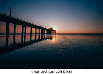 Long Exposure photo of Manhattan Beach Pier from the side with the reflective wet sand during sunset in Manhattan Beach, California