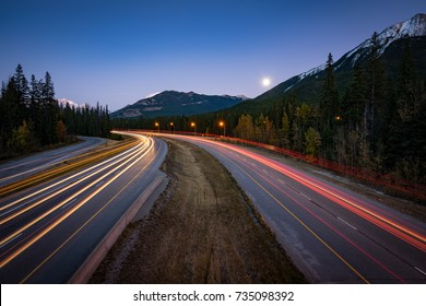 Long exposure photo taken of red and white car light trails on the Trans-Canada highway through the Rocky Mountains of Alberta.