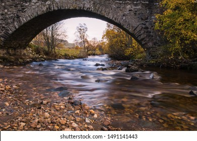 Long exposure photograph under the old military bridge along the 18th century military road in Perthshire in Scotland. Long exposure photograph of creek. Autumnal scene in the background. Orange color