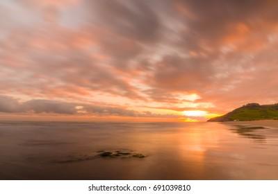 Long exposure photography. Beautiful sunrise within Playa de la Vega beach, Ribadesella, Asturias, Spain