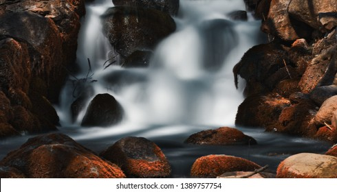Long exposure photography of running water between rocks on a mountain trail. Color graded for different effects.