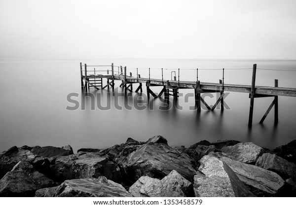 Long exposure photography of a wooden pier with rocks in front taken in Belfast, Northern Ireland