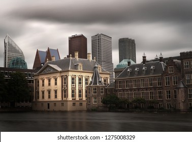 Long exposure picture of the historic Mauritshuis, Torentje and Binnenhof in The Hague, Netherlands, with modern government buildings in the backgrond, against a dark grey sky.