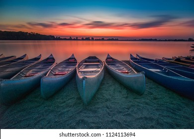 Long exposure picture of Sunset over Creve Couer lake with boats in foreground in Creve Couer, Missouri, USA