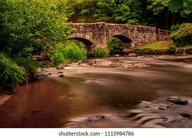 Long exposure of a river flowing under a bridge in Dartmoor National Park