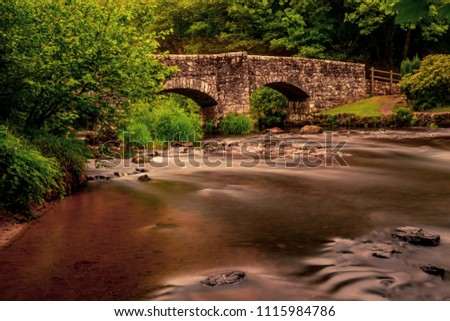 Long exposure of a river flowing under a bridge in Dartmoor National Park
