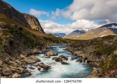 Long exposure of a river with stones in front of mountains while walking Kungsleden (Kings path) hike in northern Sweden during summer.