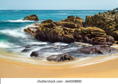Long exposure of rocks and moving waves on the Organo beach in Huatulco, Mexico.