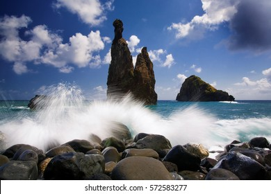 A long exposure from the rocky shore of the coast of Madeira island. Dramatic seascape, rocks hit by waves against silhouette of two steep cliffs. Low angle photo. Ribeira da Janela, Madeira seascape.