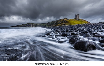 Long exposure of the sea and basalt rocks on the Northumberland coastline with Dunstanburgh Castle in background