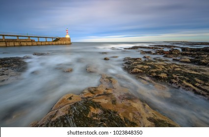 Long exposure of the sea and rocks surrounding Amble pier, Northumberland, England
