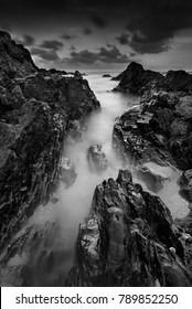 Long exposure seascape and rocky beach in black and white. Nature composition. A slow shutter speed was used to see the movement ( Soft focus due to long exposure shot ).