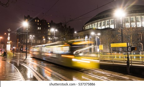 Long exposure shot in the city center of Manchester, UK with fast moving Metrolink tram in front of Manchester Central Library.