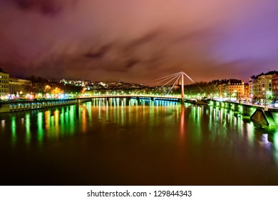Long exposure shot of a cloudy night in Lyon city center, France. View to Passerelle du Palais de Justice and Saone river.
