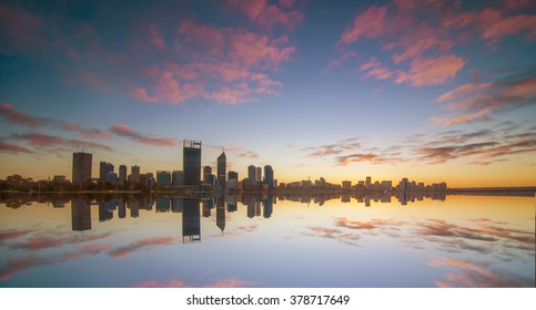 Long Exposure Shot of Golden Sunrise View of Perth Skyline from Swan River with Full Reflection. Motion Blur and Soft Focus due to Long Exposure Shot
