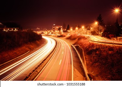 """Long exposure shot of an highway at night with vehicles light trails, public lighting and building on the right, in the city of """"Fribourg"""" in Switzerland"""