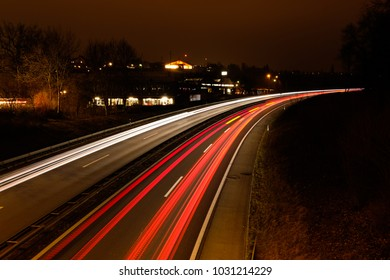 """Long exposure shot of an highway with red and yellow car light trails and trees on the sides , in the city of """"Fribourg"""" in Switzerland"""