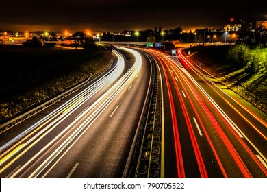 """Long exposure shot of an highway with red, white and yellow vehicles light trails, in the city of """"Fribourg"""" in Switzerland"""
