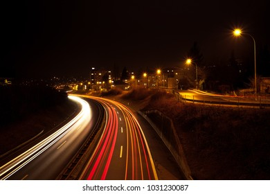 """Long exposure shot of an highway with vehicles light trails, with  public lighting in the background, in the city of """"Fribourg"""" in Switzerland"""