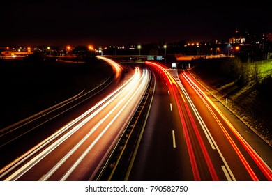 """Long exposure shot of an highway with vehicles red and orange light trails, in the city of """"Fribourg"""" in Switzerland"""