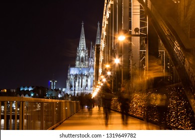 Long exposure shot of Hohenzollern bridge in Cologne with Cologne Cathedral in background and blurred people moving