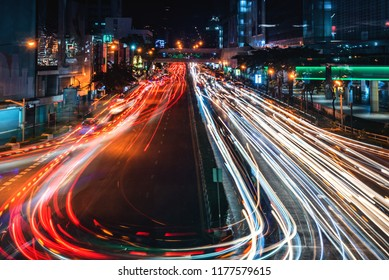 Long exposure shot image of car light trails from heavy traffic on the street in central Thailand's business area.