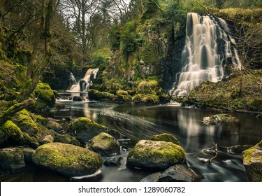 Long exposure shot of Linn Jaw Waterfalls, near Livingston, Scotland, with mossy rocks in the foreground and surrounding the waterfalls and white foam streaks in the water. West Lothian. UK. Nature
